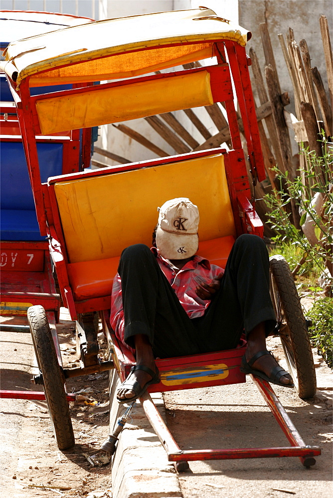 A pousse-pousse driver has a rest  on a street in Antsirabe, Madagascar, Africa