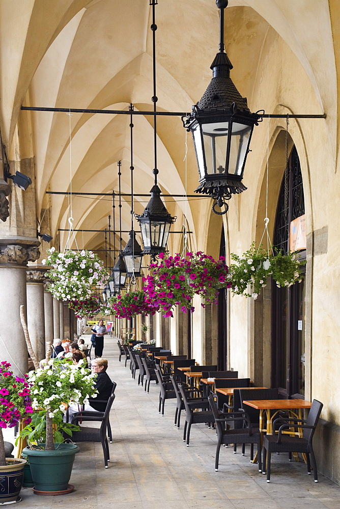 Hanging baskets outside a cafe on a arched walkway outside the Cloth Hall (Sukiennice), Rynek Glowny (Town Square) Krakow, Poland, Europe