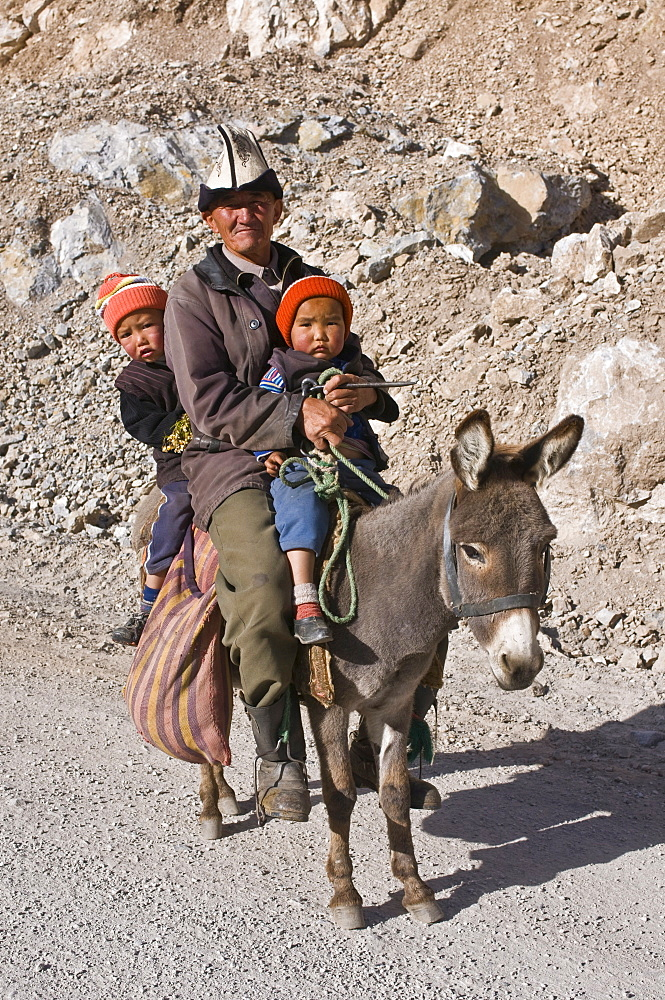 Old Kyrgyz man riding with twins on a donkey, Gulcha, Kyrgyzstan, Central Asia, Asia