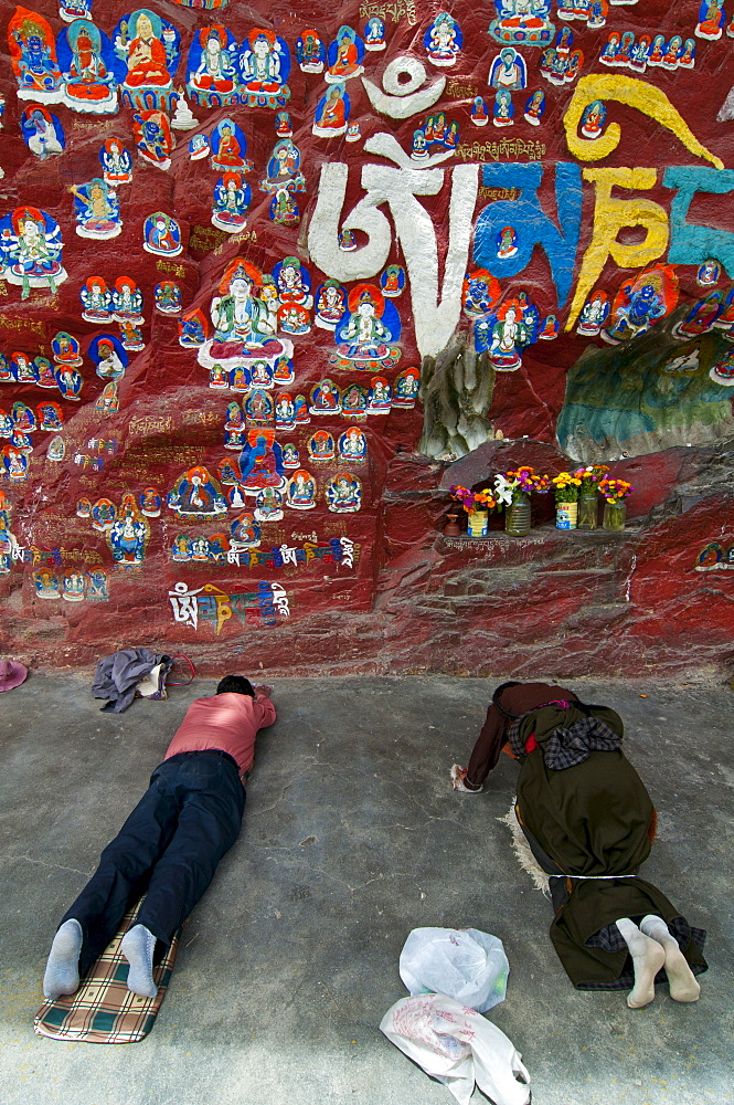 Pilgrims praying before the Blue Buddha in central Lhasa, Tibet, China, Asia
