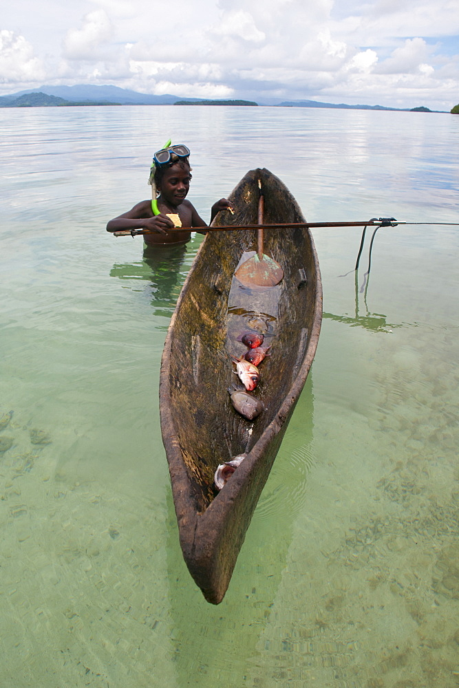 Young boy goes fishing with his canoe and harpoon, Marovo lagoon, Solomon Islands, Pacific