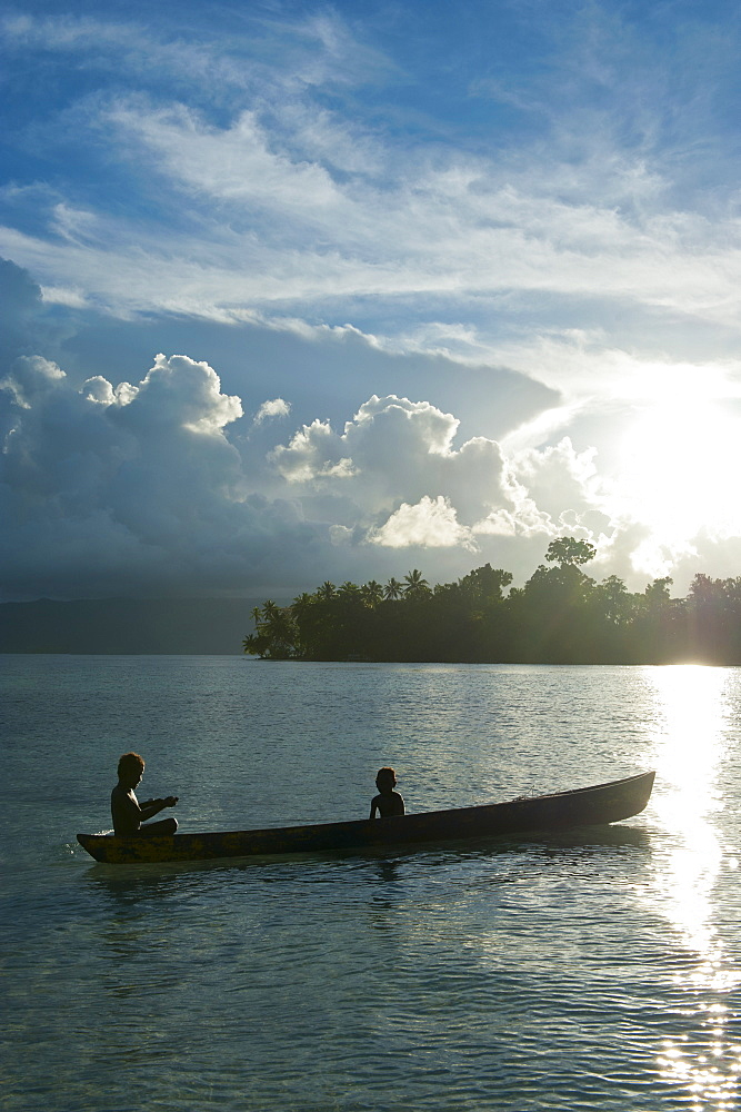 Boys in a canoe in backlit in the Marovo Lagoon, Solomon Islands, Pacific