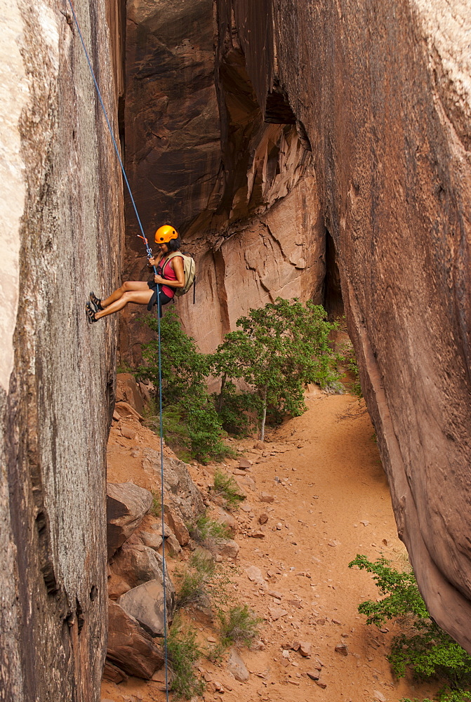 Tourist hanging on a rope while Canyoning in the area of the Slickrock Trail, near Arches National Park, Moab, Utah, United States of America, North America