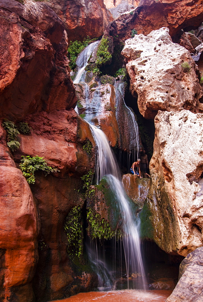 Tourist bathing in a waterfall, seen while rafting down the Colorado River, Grand Canyon, Arizona, United States of America, North America