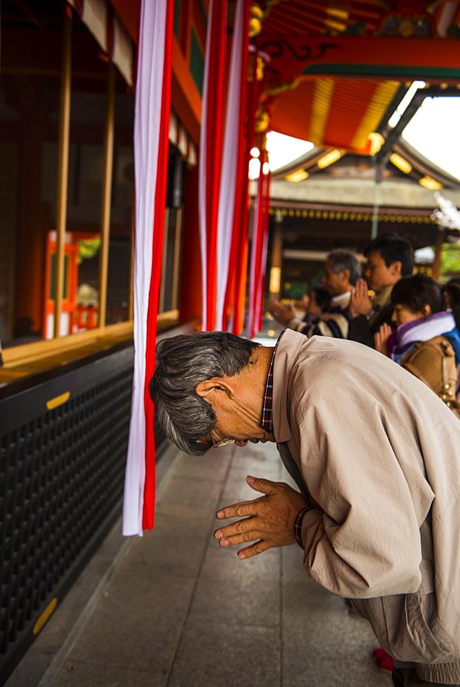 Praying pilgrim in the Endless Red Gates of Kyoto's Fushimi Inari Shrine, Kyoto, Japan, Asia