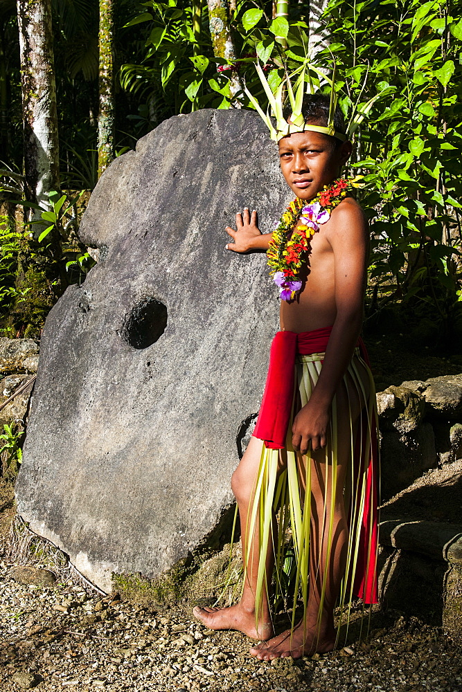 Young boy in traditional dress on the island of Yap standing before a huge stone money, Federated States of Micronesia, Caroline Islands, Pacific