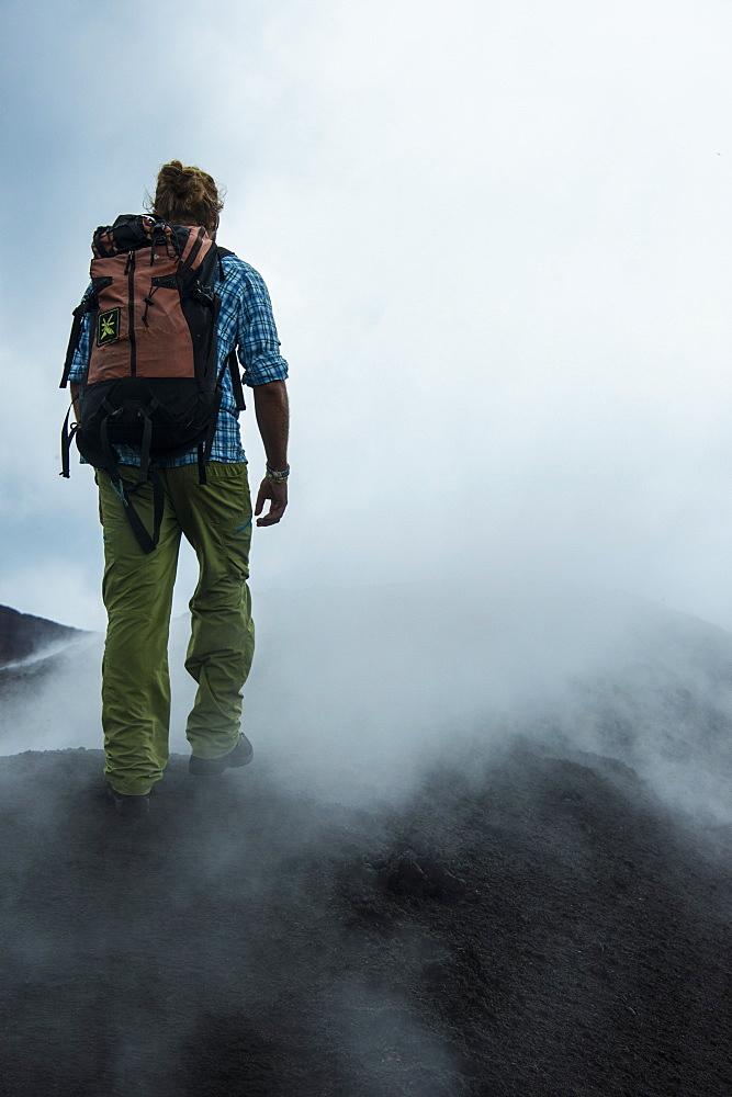 Tourist walking through sulphur smog on the Tolbachik volcano, Kamchatka, Russia, Eurasia
