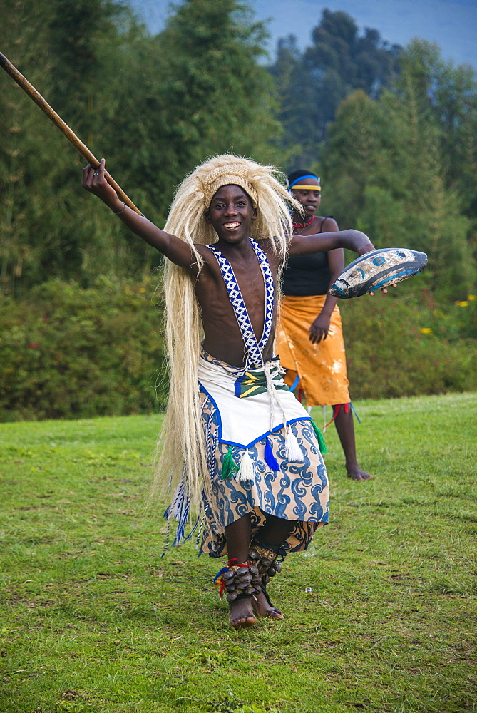 Man carrying a wig and a spear at a ceremony of former poachers, in the Virunga National Park, Rwanda, Africa