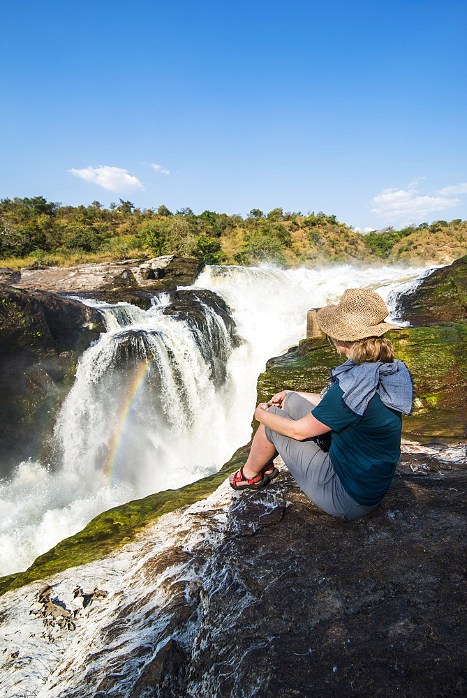 Woman looks at the stunning Murchison Falls (Kabarega Falls), Murchison Falls National Park, Uganda, East Africa, Africa