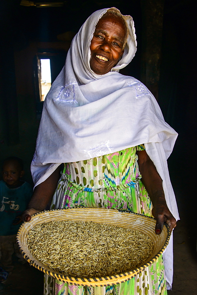 Friendly old woman standing with a basket of corn in a door frame, near Keren, Eritrea, Africa