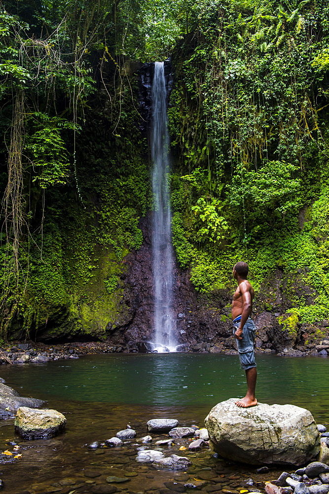 Man looking at the waterfall cascade Bombaim in the jungle interior of Sao Tome, Sao Tome and Principe, Atlantic Ocean, Africa