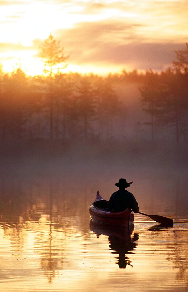 A man paddle a canoe a misty summermorning at sunrise, Byske, Vasterbotten, Sweden