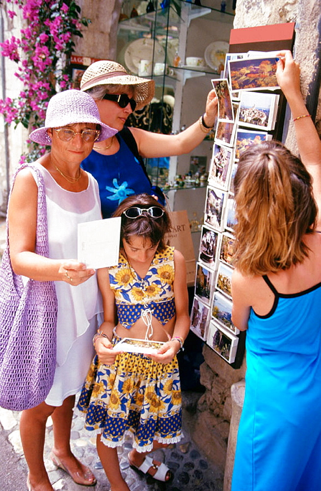 Family of visitors buying postcards, St, Paul de Vence, France