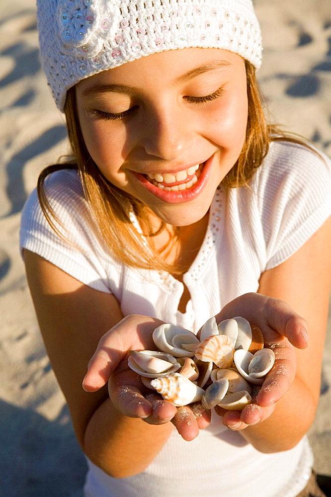 Girl with handsful of seashells