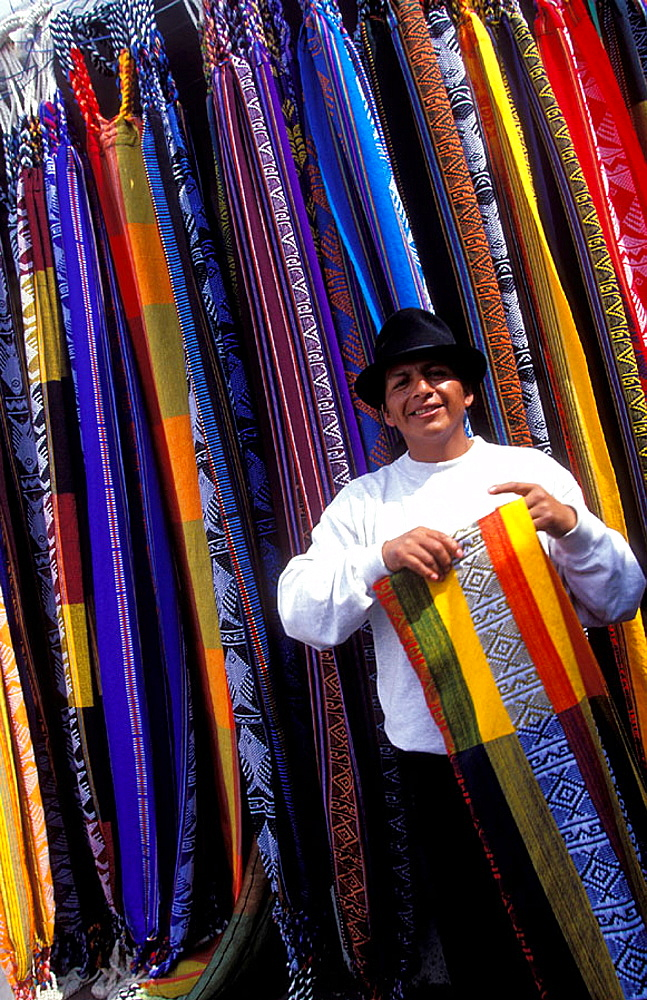 local man selling colorful fabrics at the famous Otavalo market, Otavalo, Ecuador