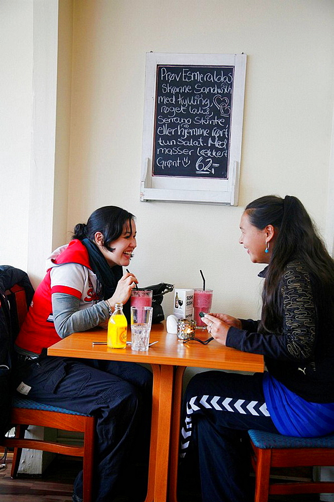 Young women sitting at Esmeralda Cafe and Restaurant in Nuuk, Greenalnd