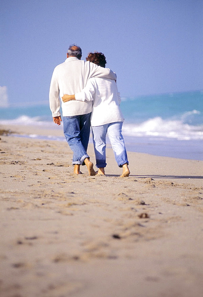 Mature couple walking at the beach wearing cloths