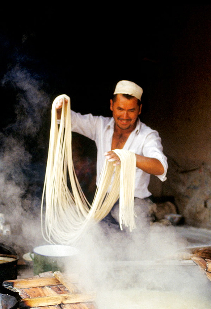 Making noodles in a small food stall on the Camel Market of Kashgar, Xingjang Province, China