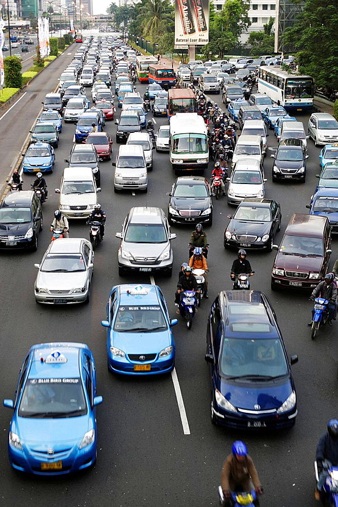 Traffic jam besides an empty bus lane for express city busses during the evening rush hour when everybody goes home on the main thoroughfare of Jakarta, Jalan Sudirman, in the heart of the Central Business District, Jakarta, Southeast Asia