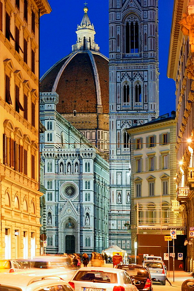 Duomo, Cathedral Santa Maria del Fiore and Campanile di Giotto seen from the street with people walking and cars parked at streetsite and at the night with streetlights on, Florence (Firenze), Tuscany, Italy, Southern Europe
