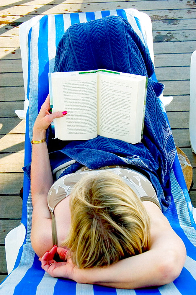 Woman reading aboard the Carnival Cruise Ship Fantasy from Port Canaveral (Florida) to the Bahama Islands - 817-146441