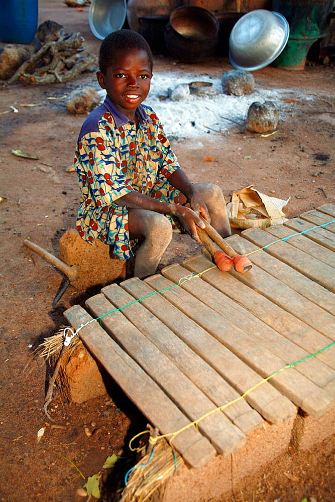 Lobi child playing balafon (typical Lobi instrument), Gaoua area, Lobi Country, Burkina Faso
