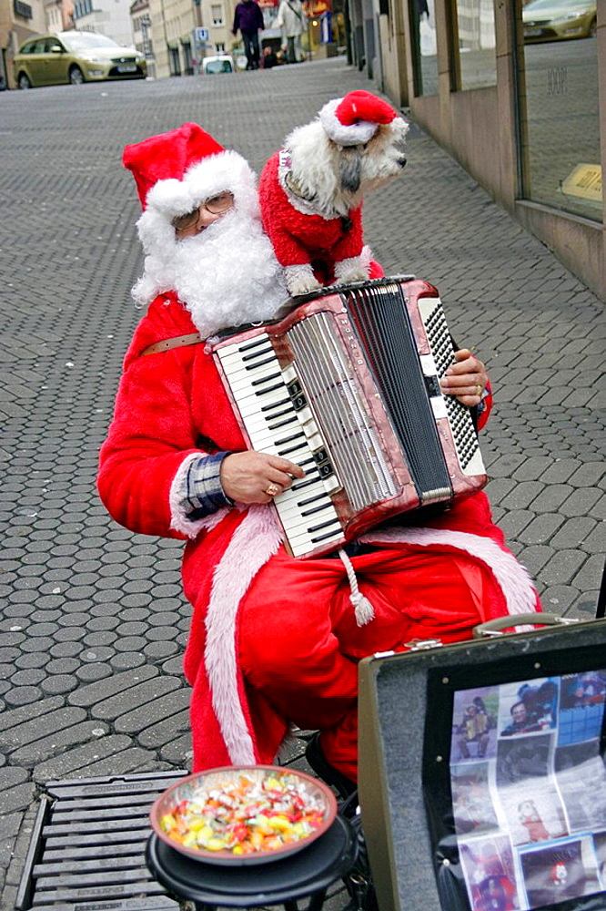 Santa Claus with his dog playing the accordian outside Christmas market, Nurnberg, Bavaria, Germany