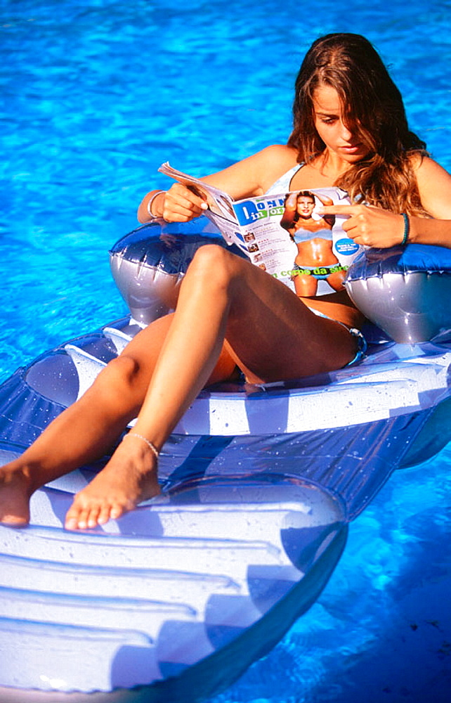 Woman reading in swimming-pool