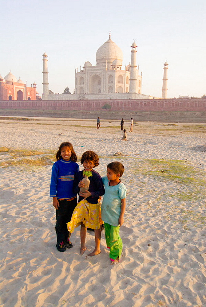 Kids standing in the sand, with group of boys playing cricket in the background, near the banks of the Yamuna River, Taj Mahal, Agra, Uttar Pradesh, India