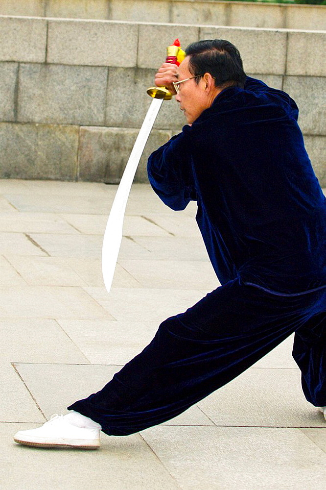 Chinese people practicing tai chi with swords in the early morning in Huangpu Park,Shanghai, China