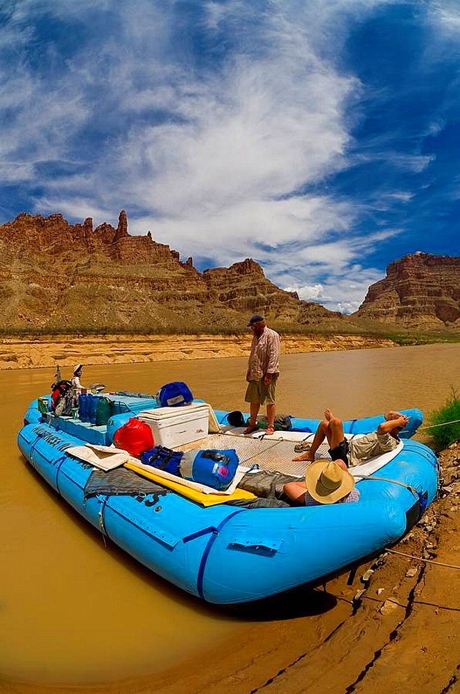 A Wilderness River Adventures motorized pontoon rafting the rapids in Cataract Canyon, stopping to camp in Upper Gypsum Canyon, the Colorado River in Glen Canyon National Recreation Area, Utah, USA