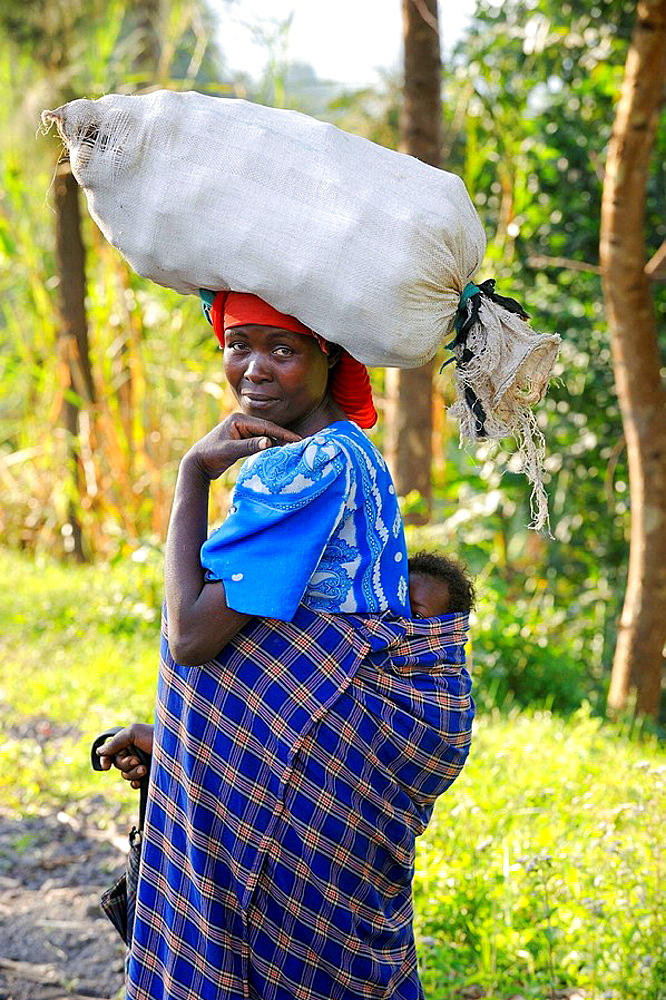 Woman on the land carrying vegetables in sac and baby on her back, Rwanda, Africa