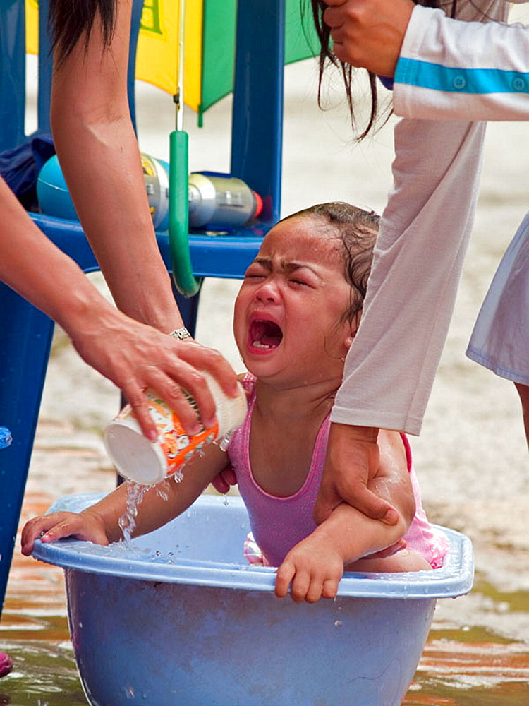 Baby cries while getting a curbside bath during the Lao Songkran New Year, Luang Prabang