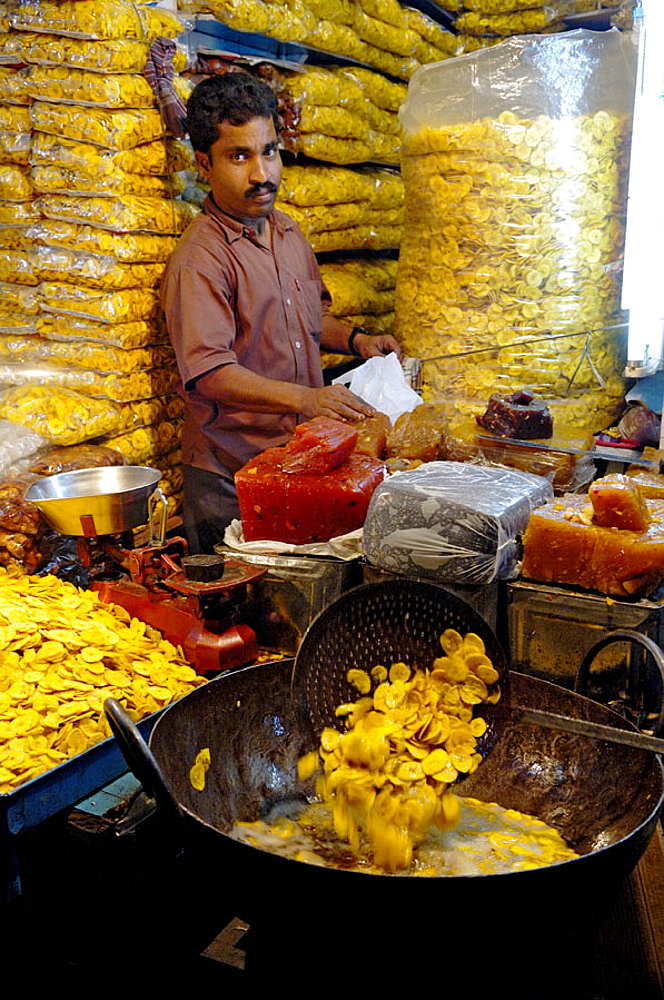 Indian man frying lots of banana crisps to sell, Kumily (Periyar), Kerala, India 2005