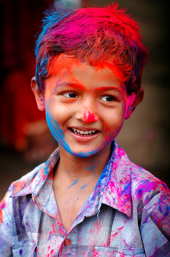 Panjim Goa, India, child covered with colored powder at Holi feast parade