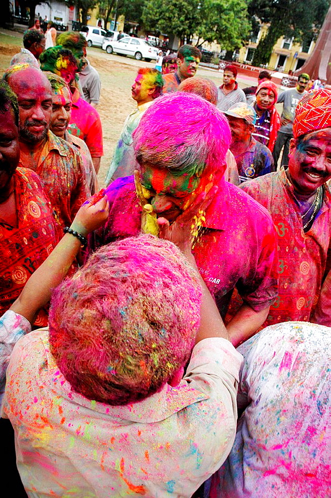 Panjim Goa, India, men putting colored powder on their faces during the Holi feast - 817-193979