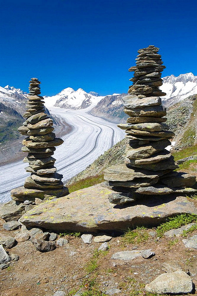 Piled stones to mark the road in the mountains  Valley glacier with its longitudinal moraines of the Glacier Alesht  At the bottom the summits of the Monch, the Junfrau and the Eiger  Berneses Alps  Switzerland