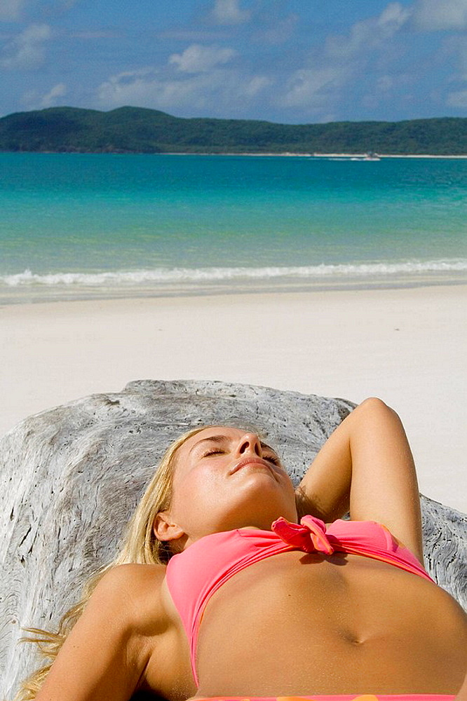 Woman sunbathing,  Whitehaven Beach, Australia
