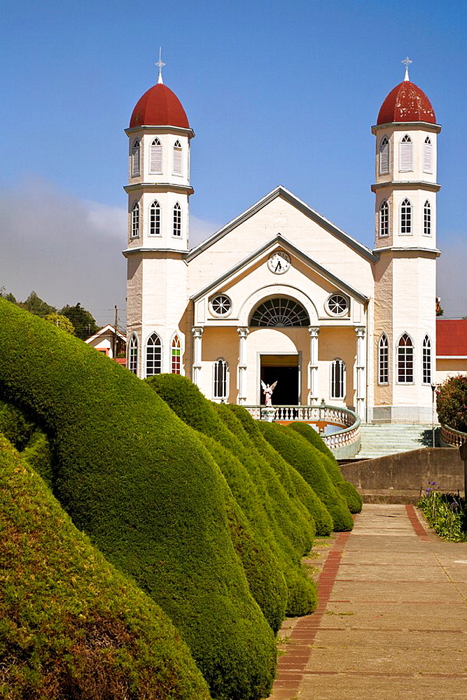 Iglesia de San Rafael behind a tunnel of arches created in the bushes by Evangelisto Blanco in Zarcero, Costa Rica