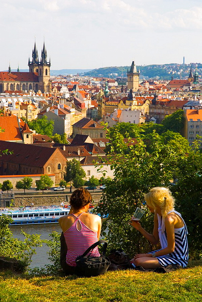 Two women relaxing in Letna Park with Old Town in background in Prague Czech Republic Europe