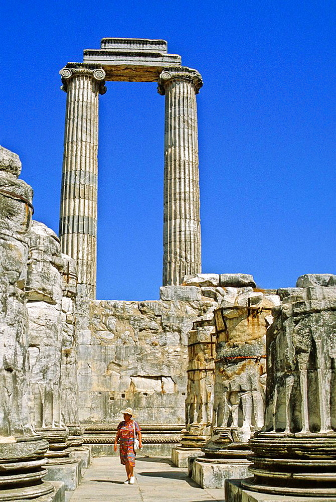 Turkey, the ruins of Didyma, Temple of Apollo, columns with ionic capitals (in background), tourist in foreground