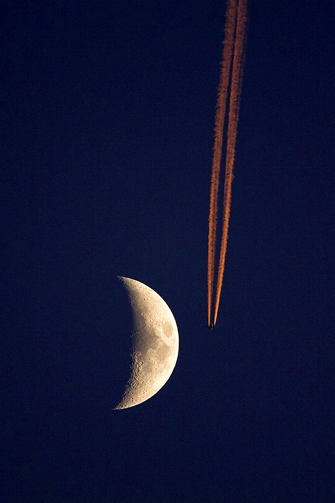 Plane, condensation trail and moon