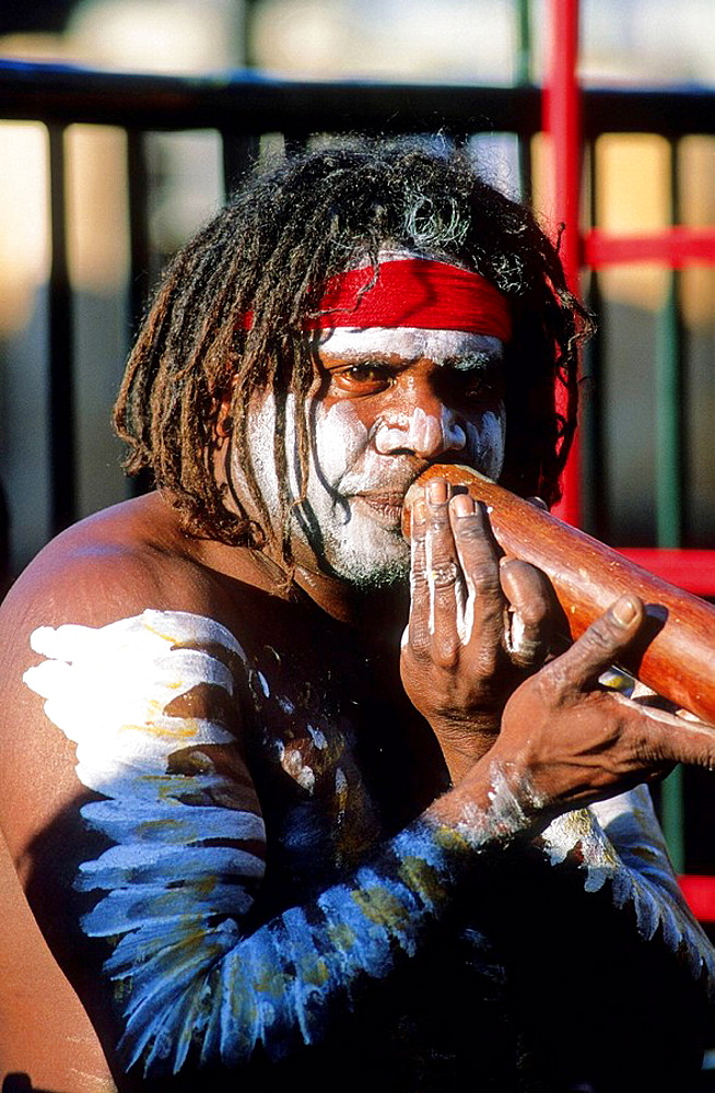 Aboriginal playing didjeridoo (or didgeridoo) musical instrument at Circular Quay, Sydney Warf Pier, Australia