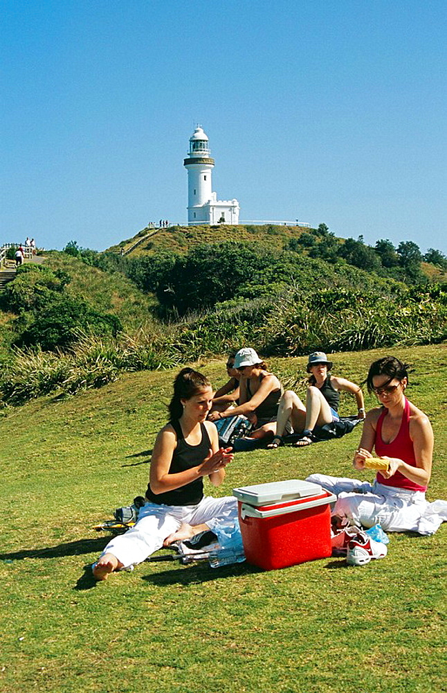 People enjoying a picnic in front of lighthouse, Byron Bay, Cape Byron, New South Wales, Australia