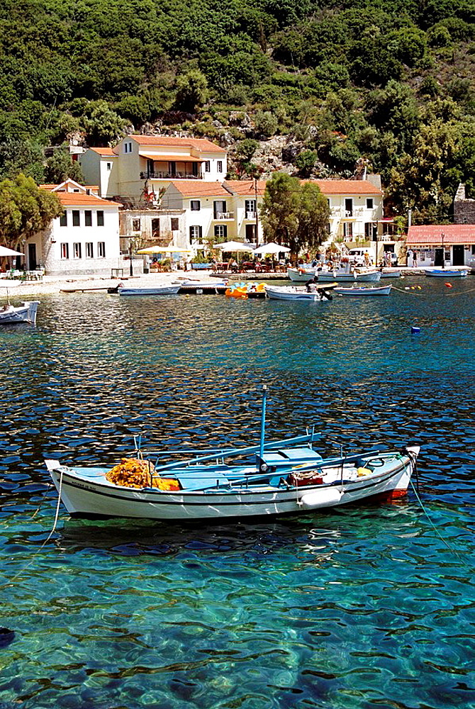 Fishing boat moored in Kioni harbour and harbourside houses and apartments, Kioni, Ithaca, Greece