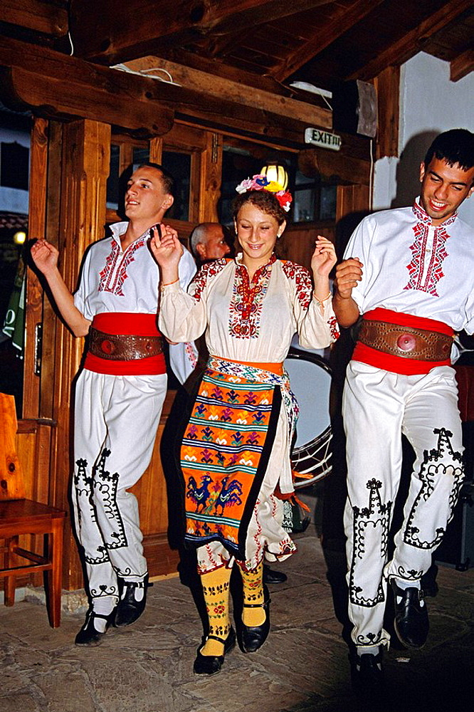 Three Dancers in national costume dancing, Arbanassi, Bulgaria