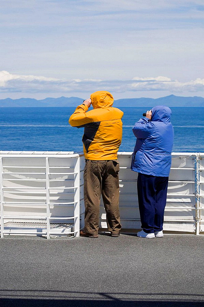 Cruise guests keep warm in jackets while whale watching in the Inside Passage during a cruise from Seattle to Alaska, USA