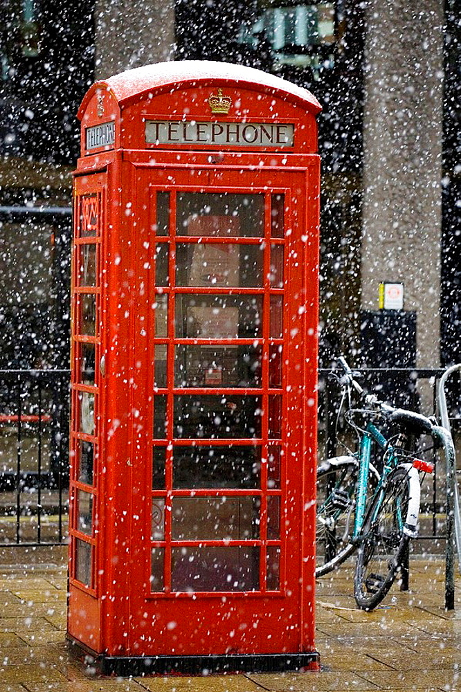 Snow falling on red telephone box in Piccadilly Circus, London, United Kingdom
