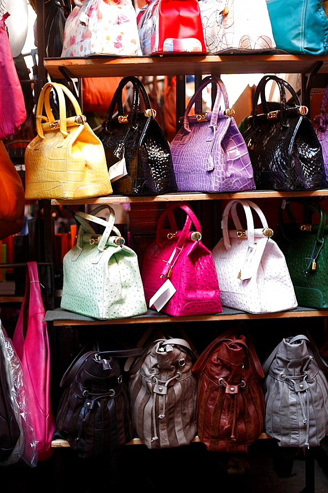Leather bags on sale on a market stall in the Tuscan city of Florence or Firenze in Italy