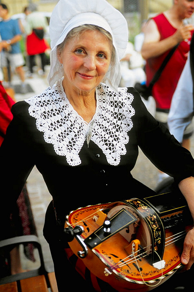 France, Perigord, Sarlat, Bastille Day, lady with traditional musical instrument